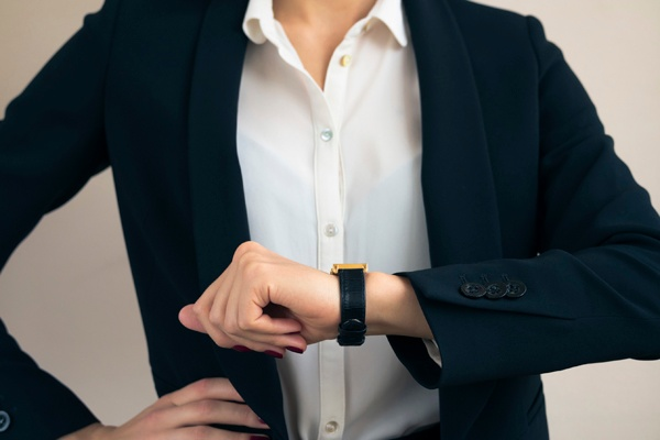 Close up of a woman looking at her watch.