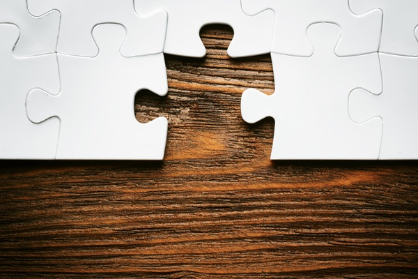 White puzzle on a wooden table with a piece missing from it.