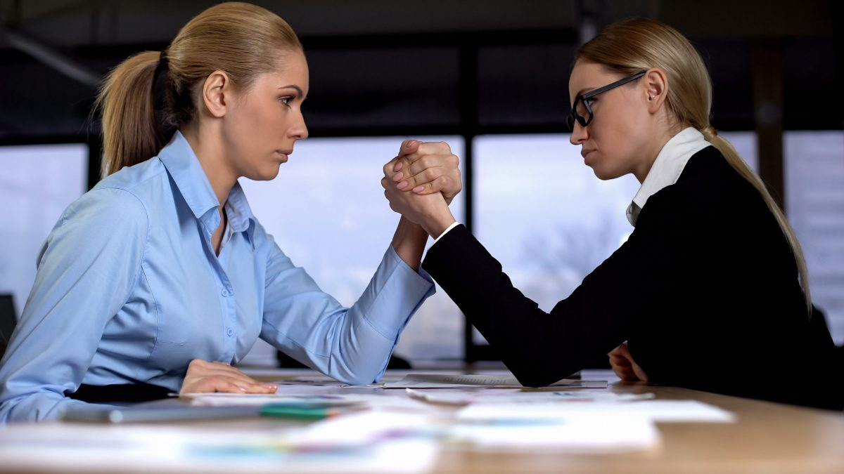 Businesses compete (two ladies arm wrestling)