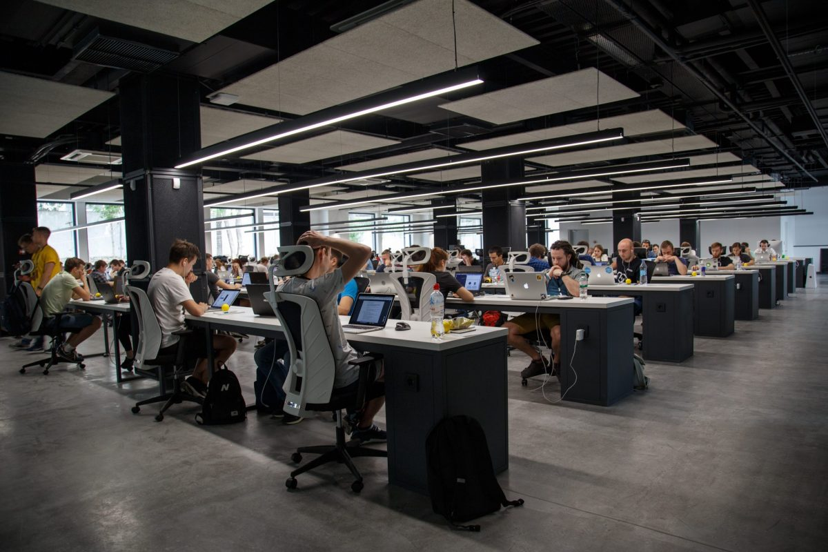 Shot of large scale office with a lot of young workers at communal desks on their computers.