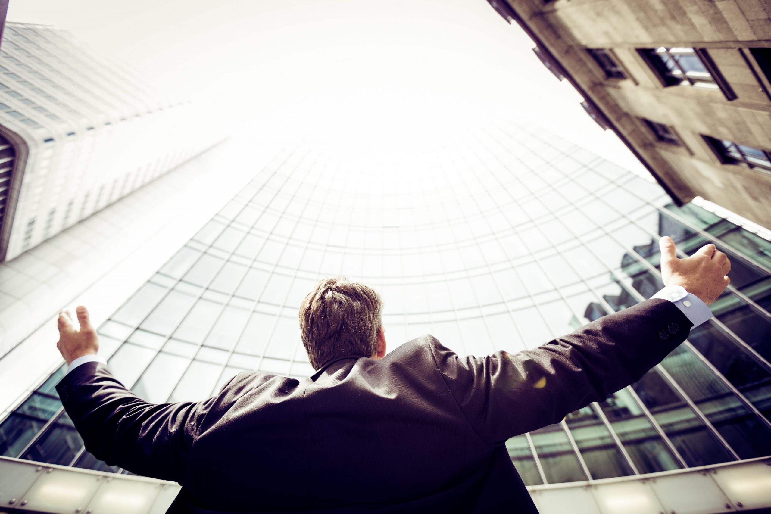 Business man with his arms in the air as he looks up at buildings in a city.