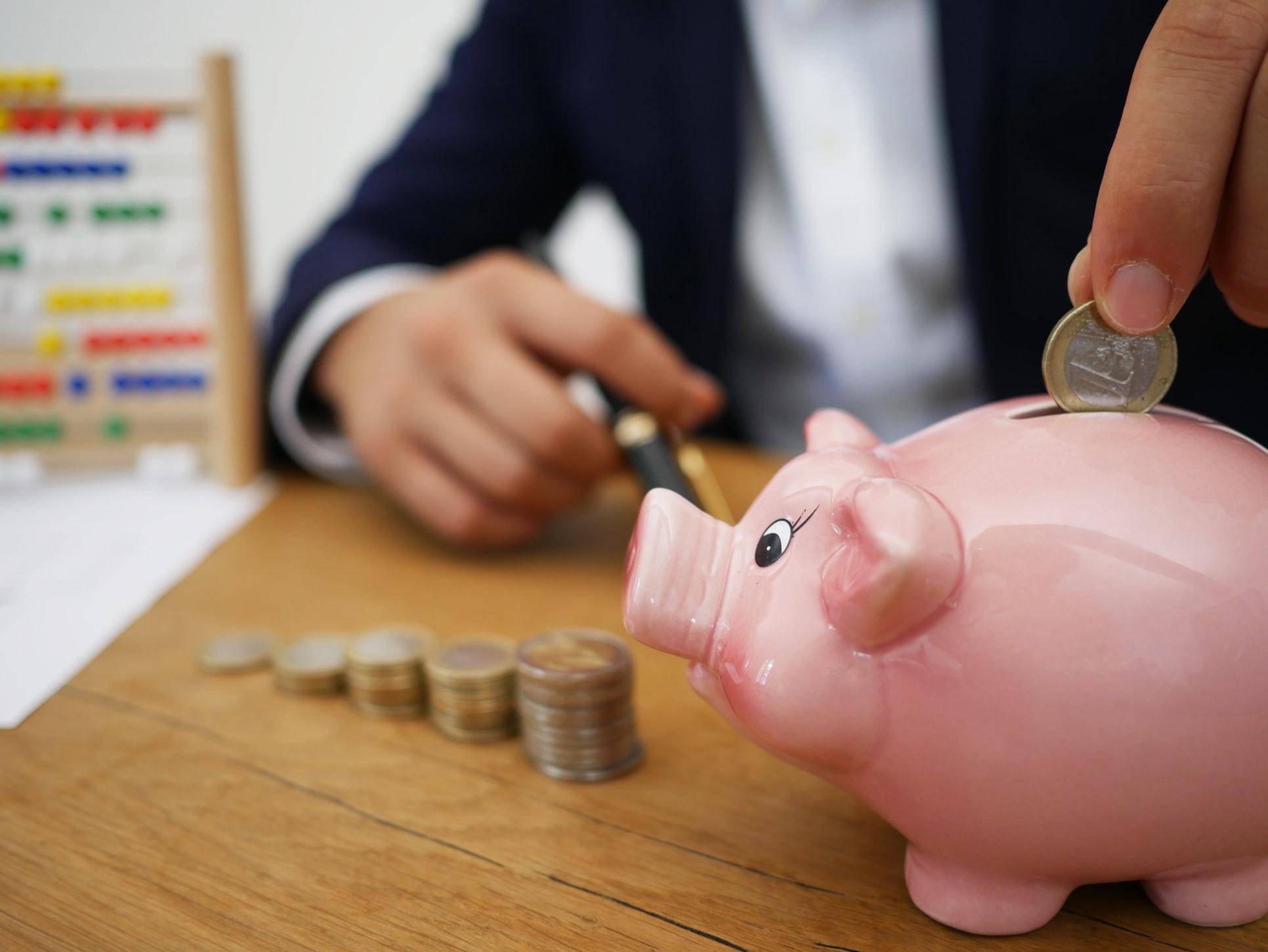 Close up of a man putting change into a piggy bank.