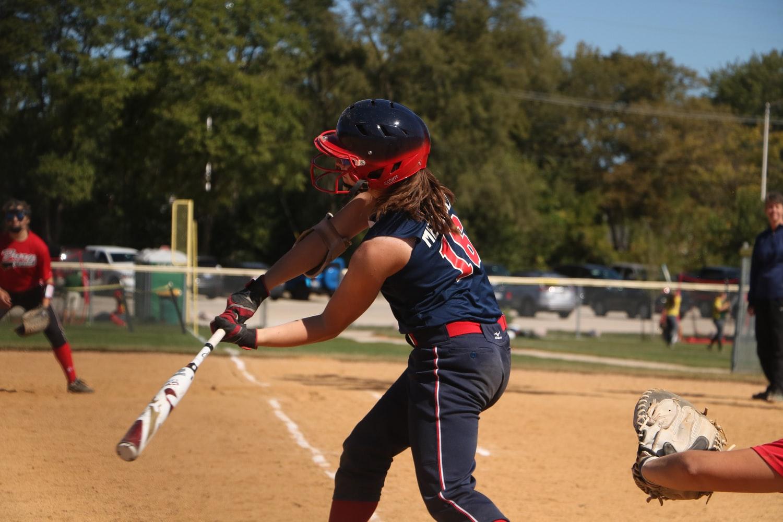 Woman hitting a ball in a softball game.