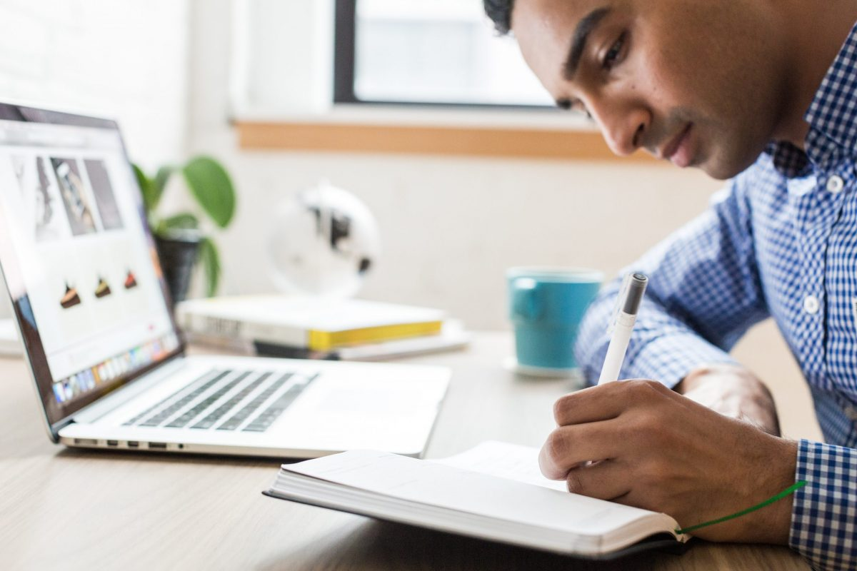 Man writing in a journal at his desk with his laptop open.