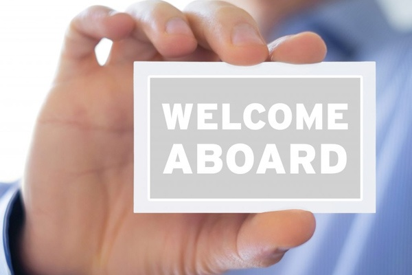 Close up of hand holding a business card saying welcome aboard